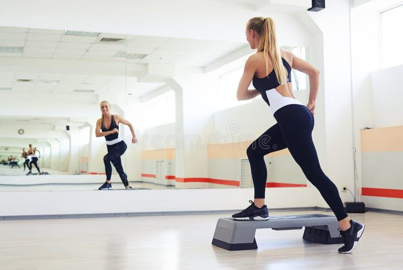 Instructor de la aptitud que hace aeróbicos del paso en gimnasio fotografía de archivo