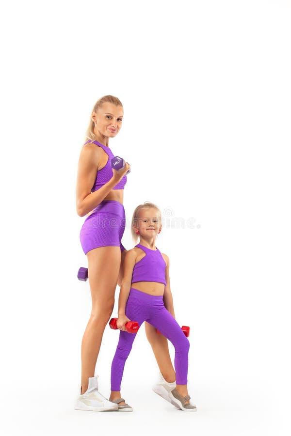 Instructor de la madre y muchacha del niño que hace ejercicios de la aptitud con pesas de gimnasia en el fondo blanco imagenes de archivo