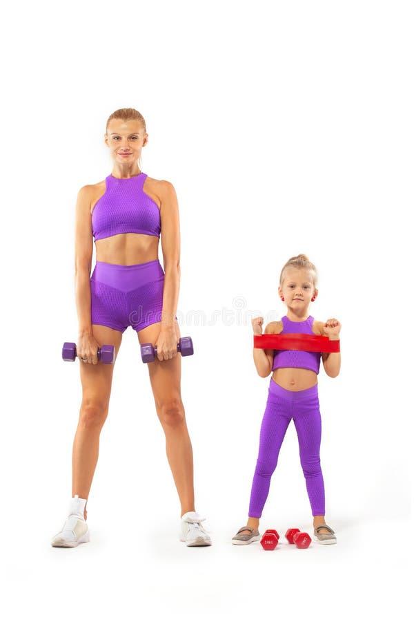 Instructor de la madre y muchacha del niño que hace ejercicios de la aptitud con pesas de gimnasia en el fondo blanco imágenes de archivo libres de regalías