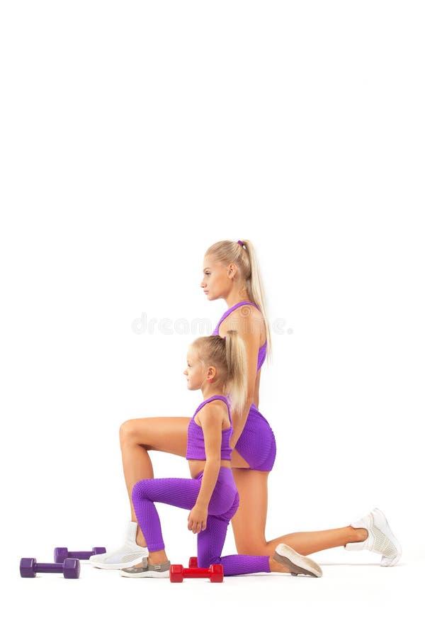 Instructor de la madre y muchacha del niño que hace ejercicios de la aptitud o de la yoga con pesas de gimnasia en el fondo blanc fotos de archivo
