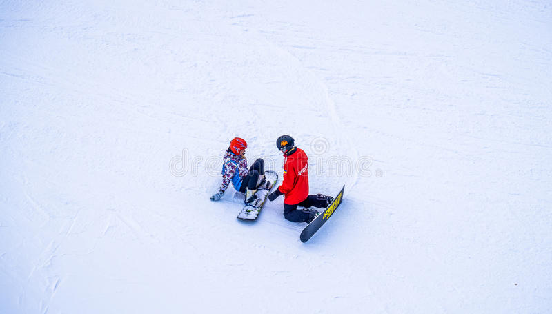 Instructor de la snowboard con su estudiante Resto en la estación de esquí foto de archivo libre de regalías