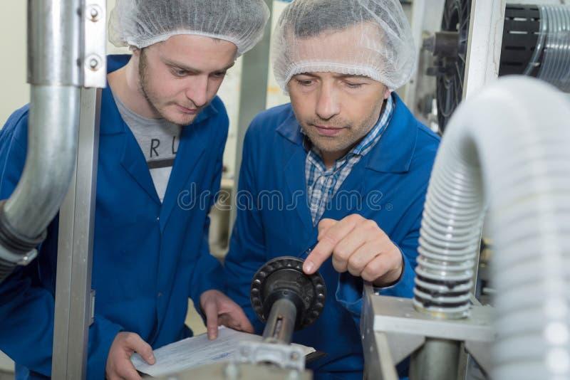 Instructor de los mecánicos que enseña al hombre joven en aprendizaje foto de archivo