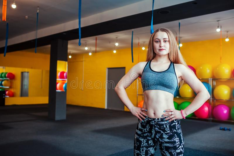 Instructor de sexo femenino joven de la aptitud que se coloca en el gimnasio Concepto juguetón de la profesión foto de archivo