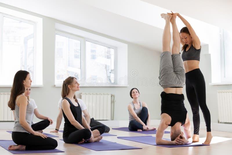 Instructor de sexo femenino joven de la yoga que enseña a una actitud de la posición del pino fotografía de archivo
