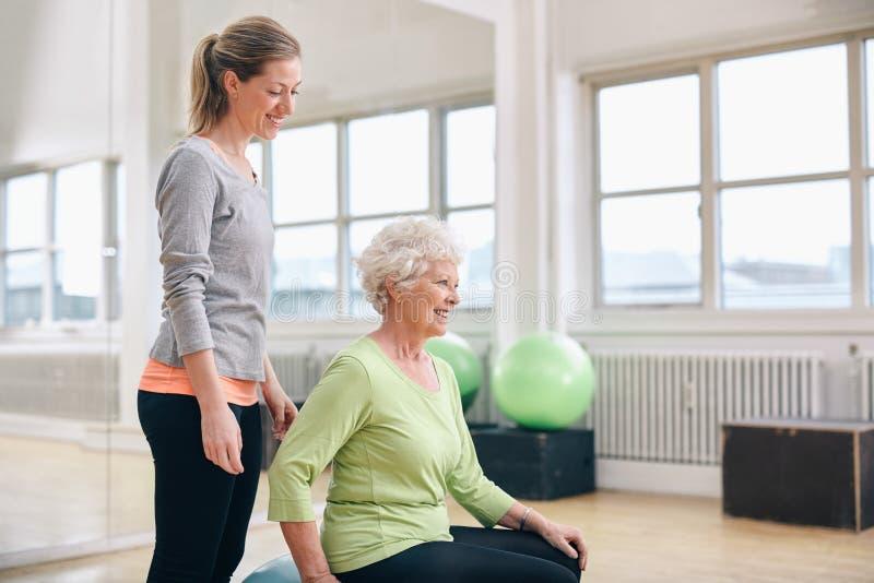 Instructor de sexo femenino que ayuda a la mujer mayor que ejercita en gimnasio fotografía de archivo libre de regalías