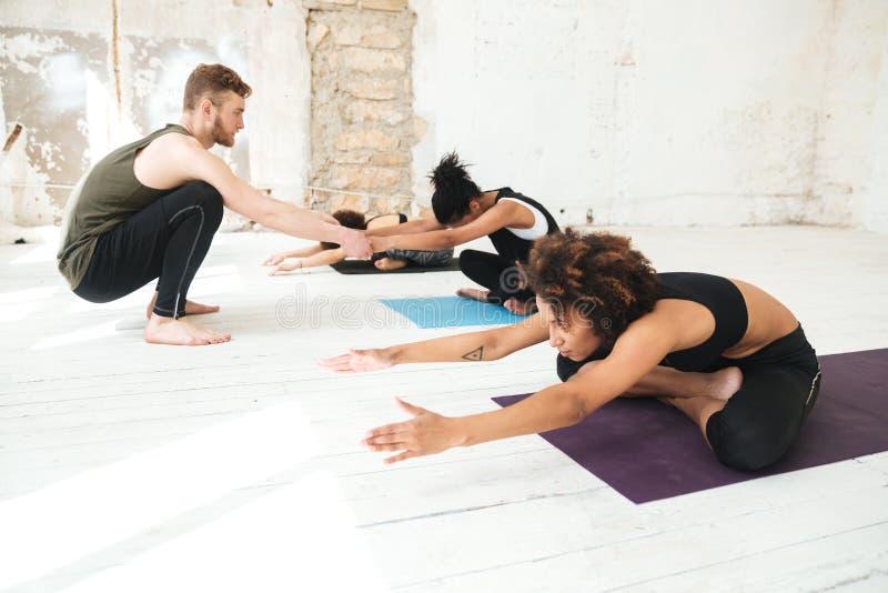 Instructor de sexo masculino de la yoga que ayuda a una mujer a hacer estiramientos de la yoga fotografía de archivo libre de regalías