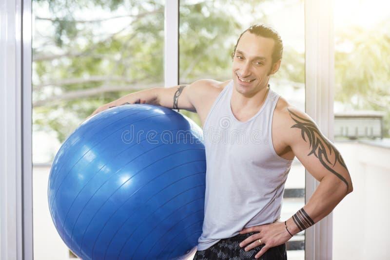 Instructor del gimnasio con la bola de la aptitud imágenes de archivo libres de regalías