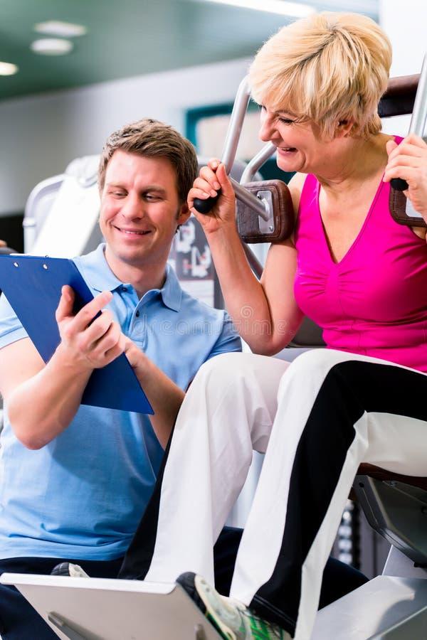 Instructor en el gimnasio que ayuda al ejercicio mayor de la mujer imagen de archivo