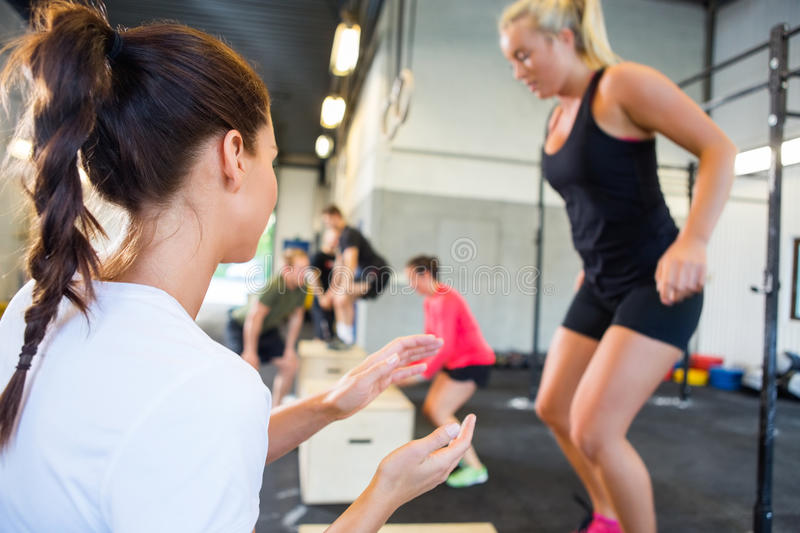 Instructor Encouraging Athlete In Box Jumping stock images