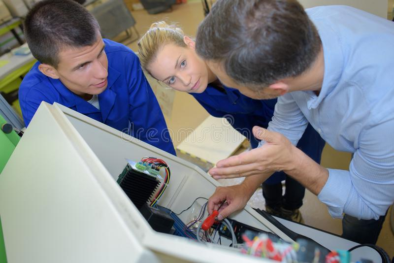 Instructor explaining wiring to trainee electricians stock images