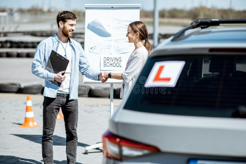 Instructor with female student at the driver`s school. Male instructor shaking hand with a young female student on the training ground at the driver`s school stock photography