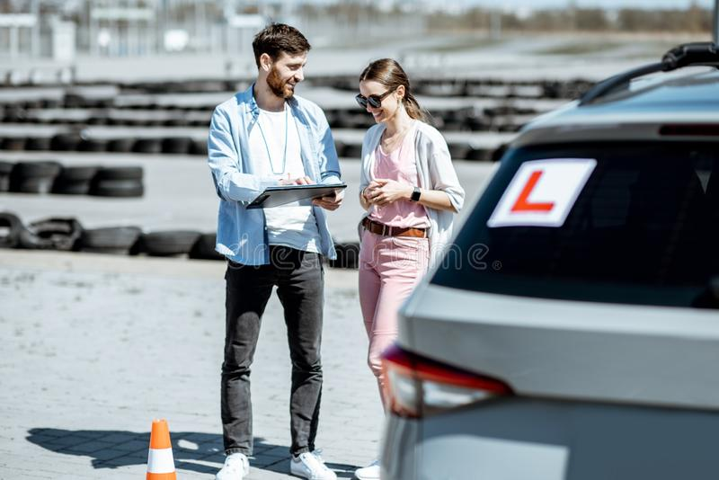 Instructor with female student at the driving school outdooors royalty free stock photo