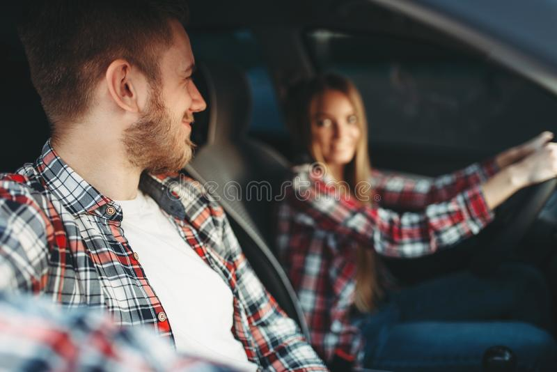 Instructor and female student smiling in vehicle stock images