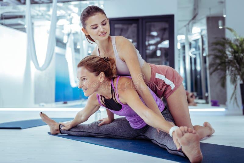 Instructor femenino experimentado que da instrucciones yoga a la mujer fotos de archivo libres de regalías