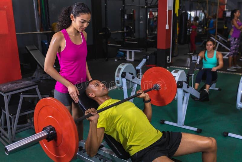 Instructor femenino que ayuda a atlético masculino para levantar el barbell en centro de aptitud foto de archivo