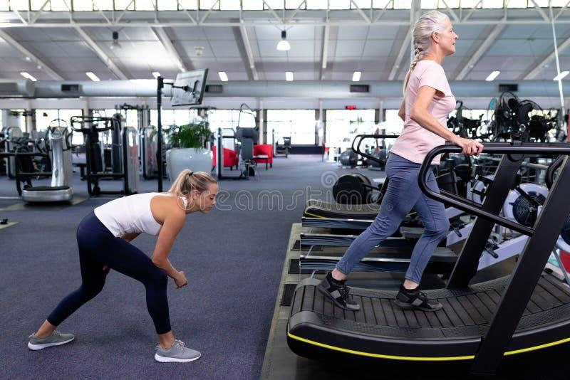 Instructor femenino que ayuda a la mujer mayor activa en la rueda de ardilla en centro de deportes moderno fotos de archivo