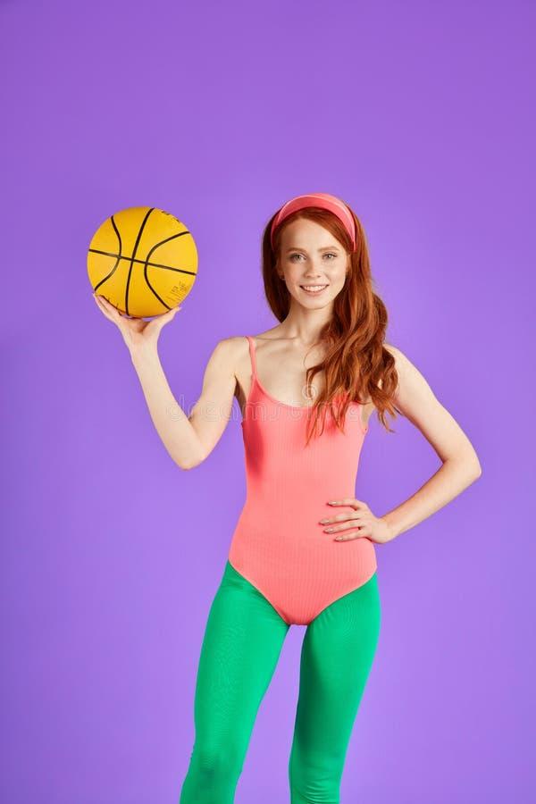 Instructor femenino que sostiene la bola anaranjada, colocándose relajada después de backetball imagen de archivo
