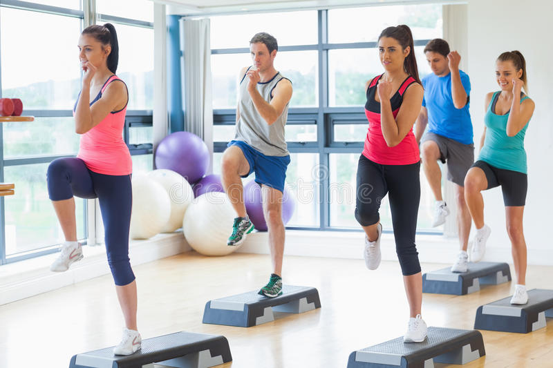 Instructor with fitness class performing step aerobics exercise royalty free stock photography