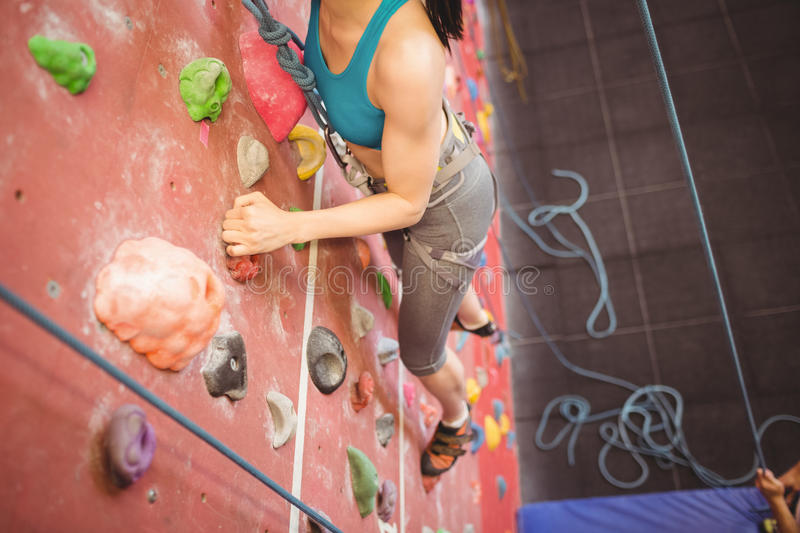 Instructor guiding woman on rock climbing wall. Instructor guiding women on rock climbing wall at the gym stock photo