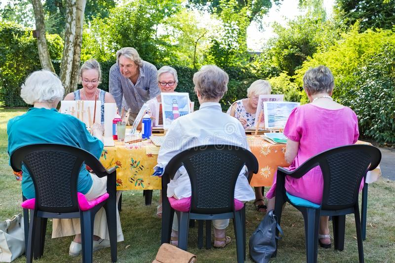Instructor helping a group of senior retired ladies at art class seated around a table painting outdoors in a garden or park. royalty free stock photo