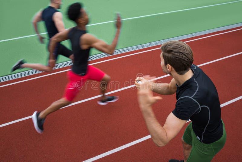 Instructor hermoso que grita cerca de grupo multiétnico joven del atleta imagen de archivo libre de regalías