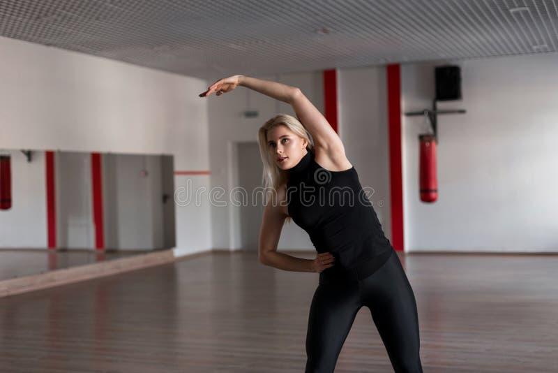 Instructor joven de la mujer profesional en la ropa de deportes negra dedicada a aptitud en el gimnasio Trenes de la muchacha den foto de archivo