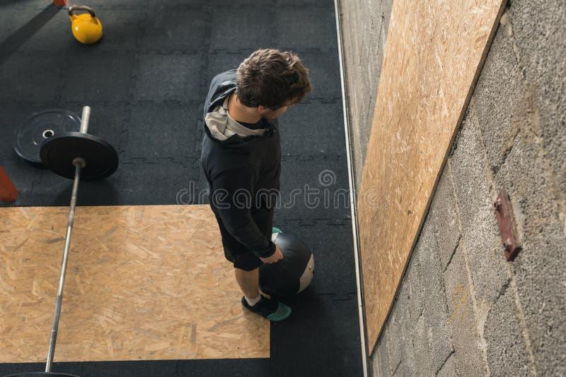 Instructor masculino de Crossfit que hace la bola de la pared foto de archivo libre de regalías