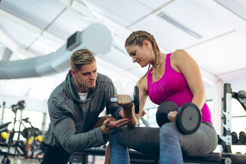 Instructor masculino que ayuda al atleta de sexo femenino para ejercitar con pesas de gimnasia en centro de aptitud imagen de archivo