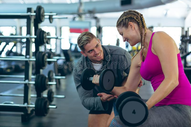 Instructor masculino que ayuda al atleta de sexo femenino para ejercitar con pesas de gimnasia en centro de aptitud fotos de archivo libres de regalías