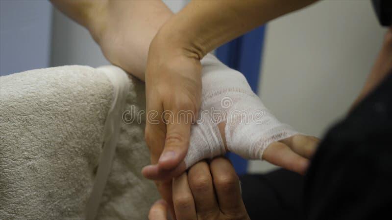 Instructor o encargado Wrapping Hands del boxeo de un cierre del boxeador encima de la profundidad del campo baja - preparándose  foto de archivo libre de regalías