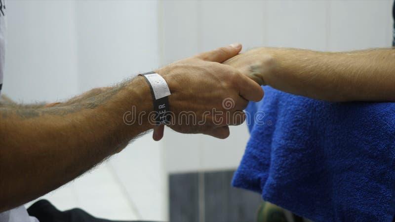 Instructor o encargado Wrapping Hands del boxeo de un cierre del boxeador encima de la profundidad del campo baja - preparándose  fotos de archivo