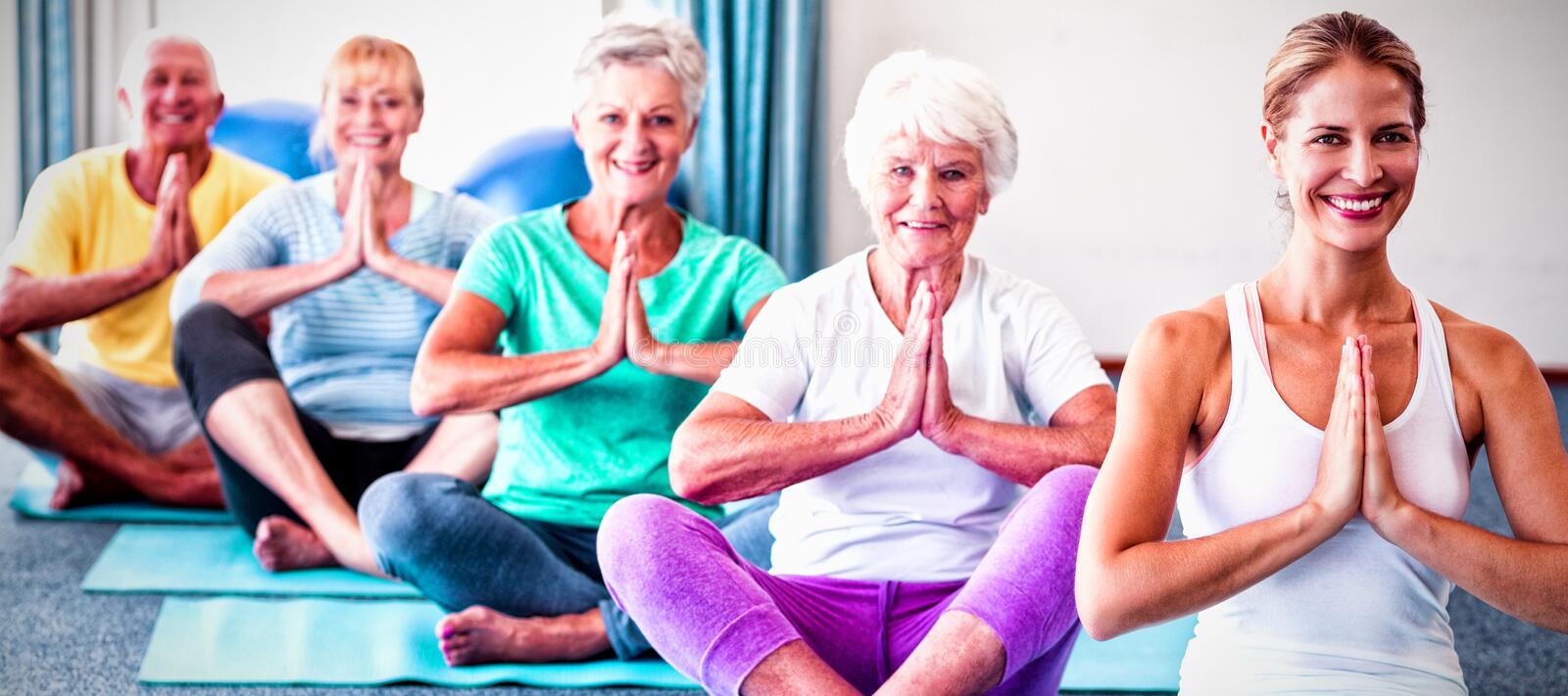 Instructor performing yoga with seniors royalty free stock photography