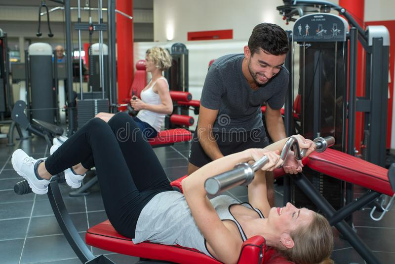 Instructor personal de la aptitud que ayuda a la mujer joven en gimnasio foto de archivo