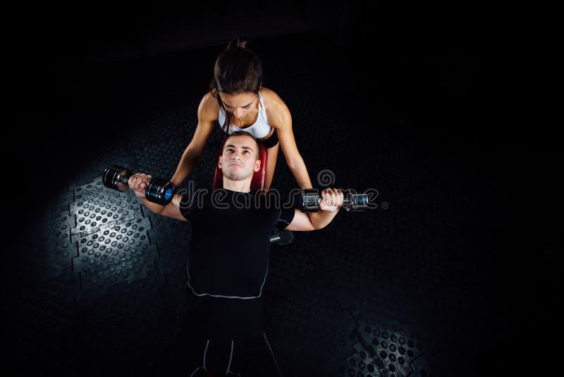 Instructor personal de sexo femenino de la aptitud que ayuda a un hombre joven en el gimnasio foto de archivo libre de regalías