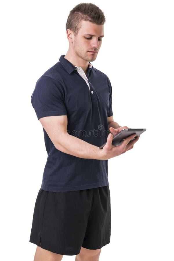 Instructor personal joven hermoso con la tableta imagen de archivo