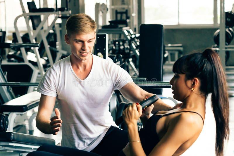 Instructor personal masculino caucásico joven en el gimnasio, cliente femenino favorable de la aptitud fotos de archivo libres de regalías