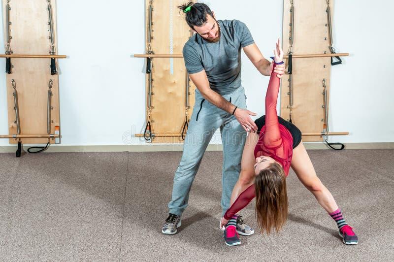 Instructor personal masculino de la yoga hermosa con una barba que ayuda a la muchacha joven de la aptitud a estirar sus músculos imagen de archivo