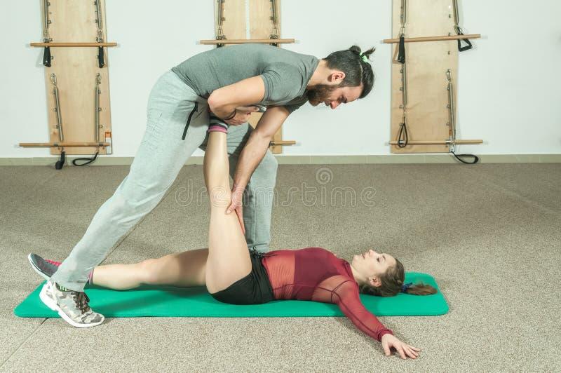 Instructor personal masculino hermoso con una barba que ayuda a la muchacha joven de la aptitud a estirar sus músculos después de imagen de archivo