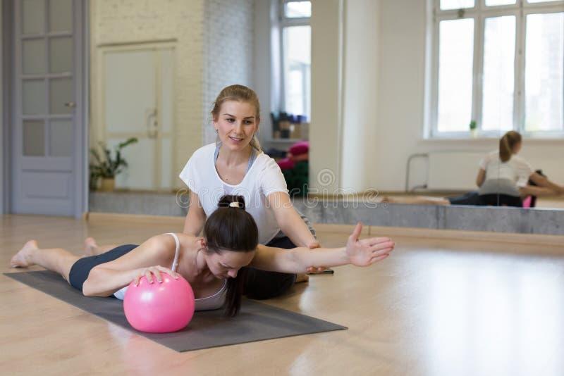 Instructor personal, pilates Dos trabajos de las mujeres con la pequeña bola apta, una ayudan a otra para hacer el exersice para  foto de archivo