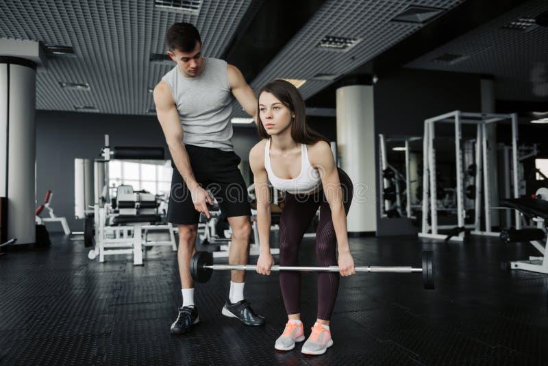 Instructor personal posiciones en cuclillas de ayuda de una mujer joven con los dumbells en un gimnasio imagen de archivo libre de regalías