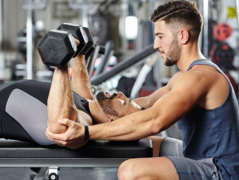 Instructor personal que ayuda a un hombre en el gimnasio fotos de archivo
