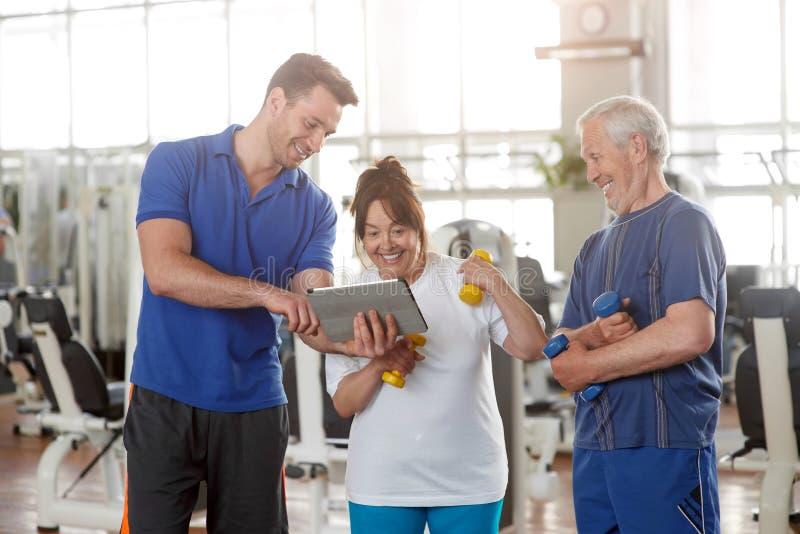 Instructor personal que da instrucciones a los pares mayores en gimnasio foto de archivo libre de regalías
