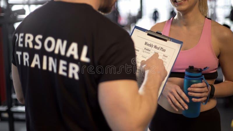 Instructor personal que discute plan semanal de la comida con el cliente femenino en el gimnasio, ayuda fotografía de archivo libre de regalías