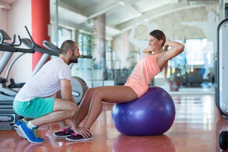 Instructor personal que entrena a una mujer en el gimnasio con la bola de la yoga fotos de archivo