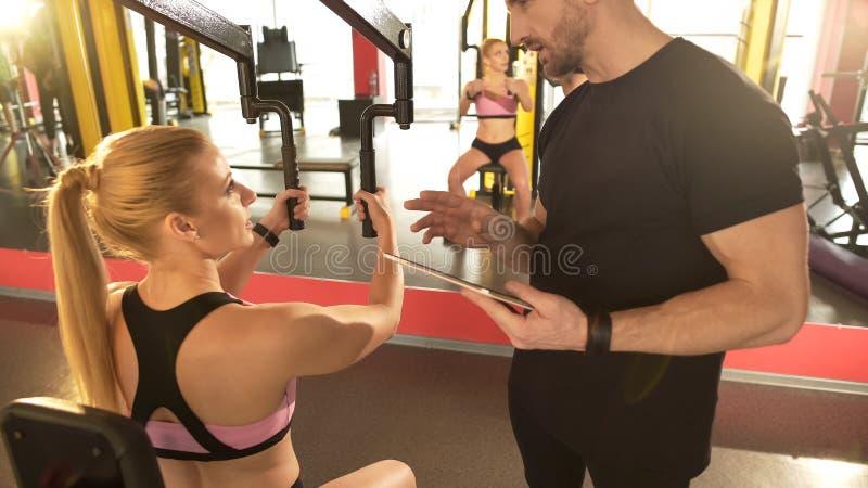 Instructor personal que habla con el cliente, dando extremidades útiles para trabajar mejor su cuerpo foto de archivo