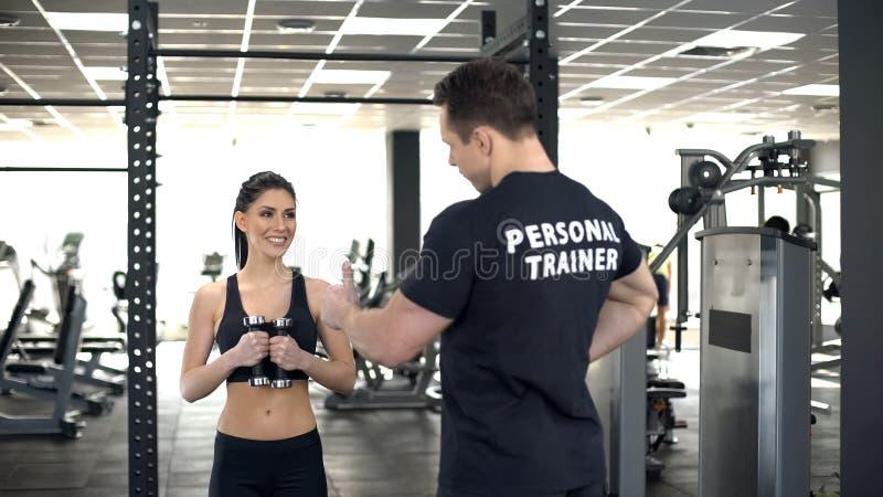 Instructor personal que muestra los pulgares hasta muchacha apta mientras que ejercita, motivación foto de archivo libre de regalías