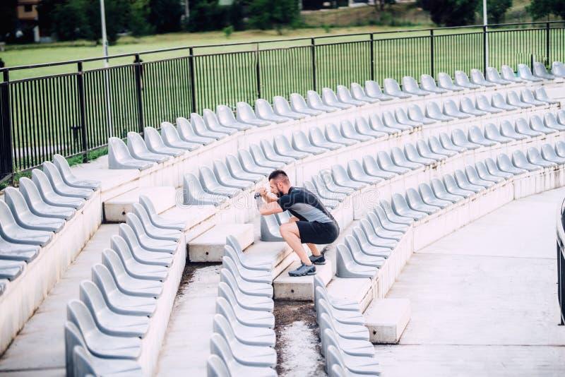 Instructor personal que se resuelve en las escaleras del estadio, haciendo entrenamiento de la pierna imágenes de archivo libres de regalías