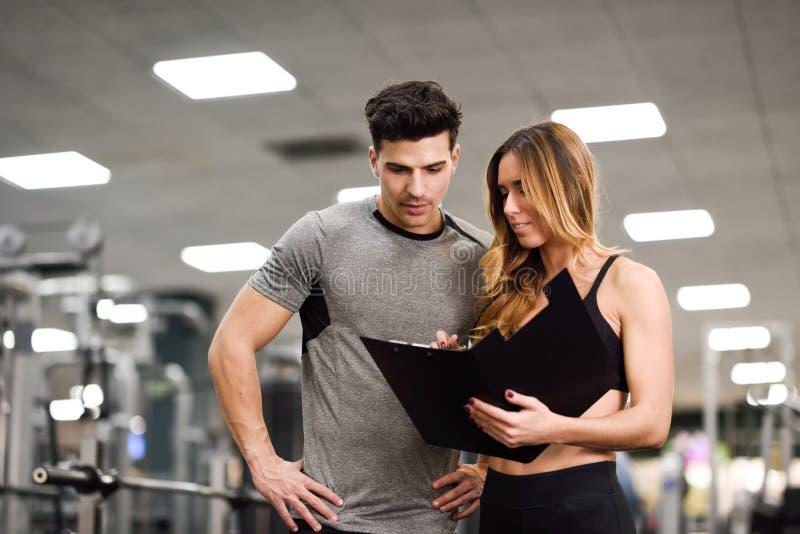 Instructor personal y cliente que miran su progreso el gimnasio imagenes de archivo