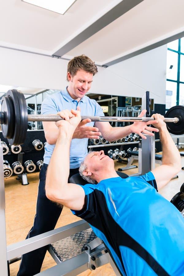 Instructor que ayuda al barbell de elevación del hombre mayor en gimnasio imagenes de archivo