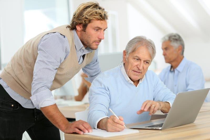 Instructor que ayuda al hombre mayor en el entrenamiento fotos de archivo libres de regalías